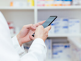 Pharmacist, Physician using a mobile phone at drugstore room. Doctor touching a cell phone in medical concept
